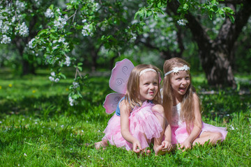 Little cute girls in the blossoming apple garden