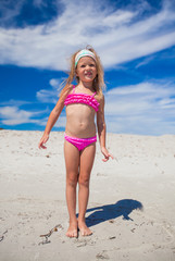 Adorable little girl in beautiful swimsuit have fun at tropical