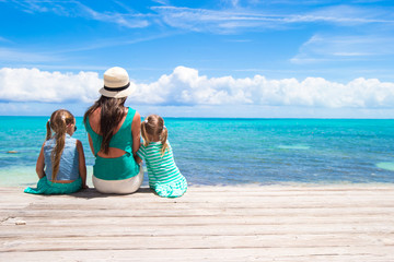 Young mother and little daughters during tropical vacation