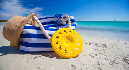 Stripe bag, straw hat, sunblock and frisbee on white sandy