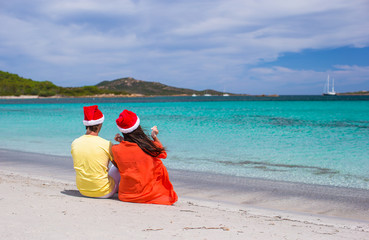 Young romantic couple in Santa hats during beach vacation