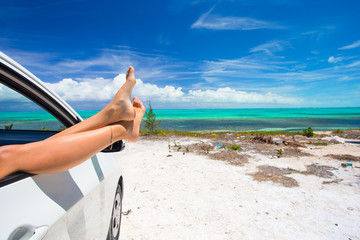 Female barefoot from the window of a car on background tropical
