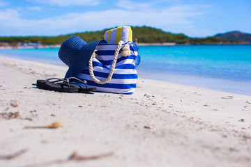 Blue bag, straw hat, flip flops and towel on white tropical