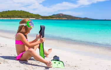 Little girl with flippers and goggles for ssnorkling on the