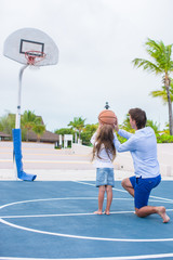Young man and little girl playing basketball outside at exotic