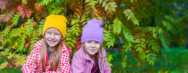 Adorable little girls at beautiful autumn day outdoors
