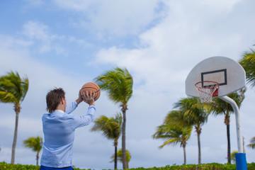 Young man playing basketball outside at exotic resort