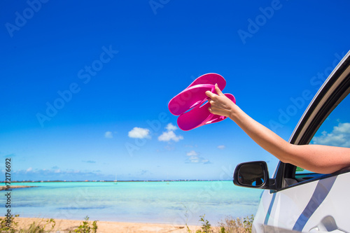 Flip Flops from the window of a car on background tropical beach - 72176692