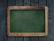 Old green menu blackboard hanging on wooden wall