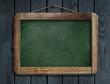 Old green menu blackboard hanging on wooden wall