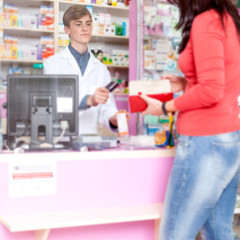 Pharmacist givind the credit card to the client