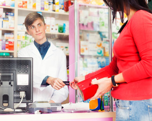 Customer paying with credit card in pharmacy