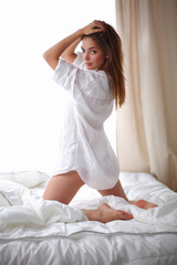 Young woman sittng in bed at home