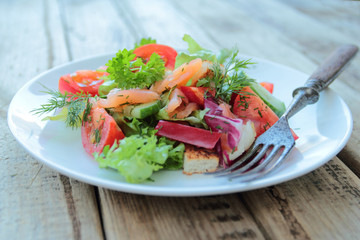 Plate with salad with salmon, fresh vegetables and herbs