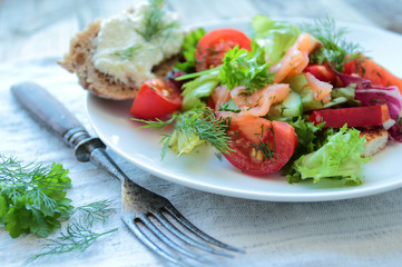 Fresh salad with salmon and vegetables on white plate