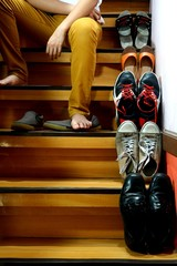 Person sitting beside Different shoes on a staircase