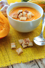 Bowl with pumpkin soup with croutons