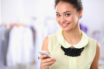 Pretty fashion designer working in office using mobile phone