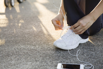 Women ready to run by connecting the straps of shoes