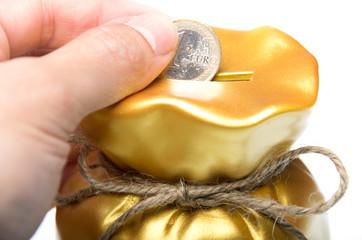 Man placing a euro coin into a piggy bank