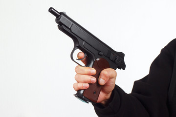 Hand with discharged semi-automatic pistol on a white background