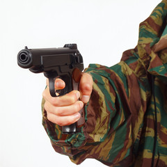 Hand in camouflage uniform with army handgun
