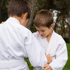 Two kids practicing judo outdoors in a park.