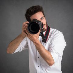 Man with camera portrait over dark grunge background.
