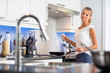 Pretty, young woman in her modern, clean and bright kitchen