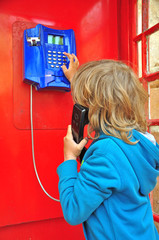 Boy in red telephone box
