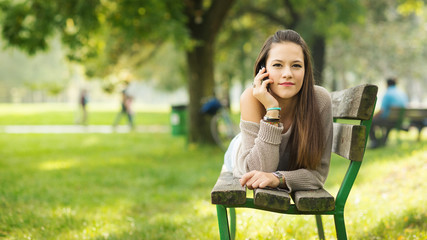 Happy young woman talking at the phone outdoors in a park with c