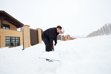 Man cleans snow shovel