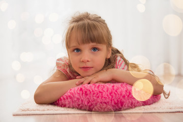 Cute little girl enjoying lying on the floor at home. Holiday li