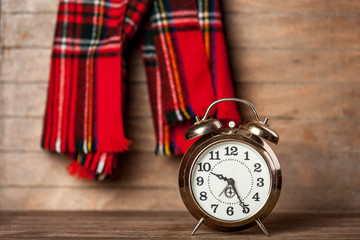 Retro alarm clock and scarf on wooden table.