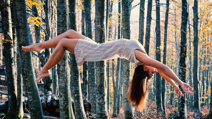 Levitation portrait of young beautiful woman in the woods.