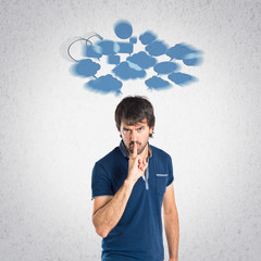 Man making silence gesture over grey background