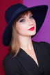 Brunette girl with hat on red and violet background.