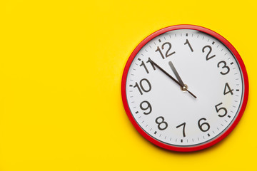 Huge red clock on yellow background.
