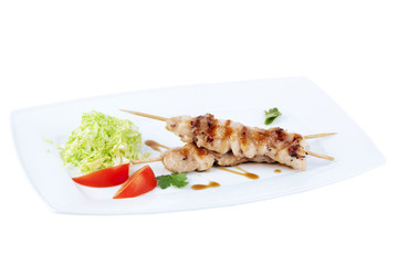 chicken kebab with cabbage and tomatoes on a square plate