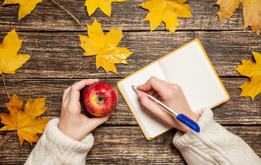Female hand writing something in to notebook and holding apple