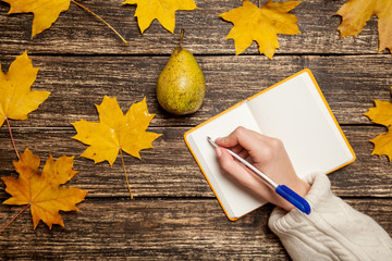Female hand writing something in to notebook near pear on a tabl