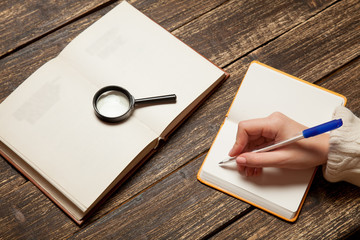 Female hand writing something in to notebook
