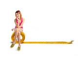 Redhead girl sitting on tape measure