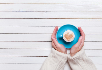 Female hands holding cup of coffee on wooden table.