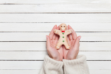 Female hands holding gingerbread on wooden table.