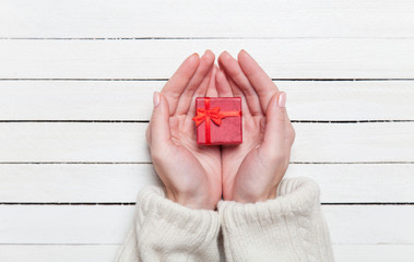 Female hands holding gift on wooden table.