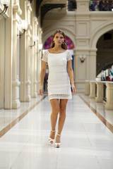 Young woman in white dress walking in the shop