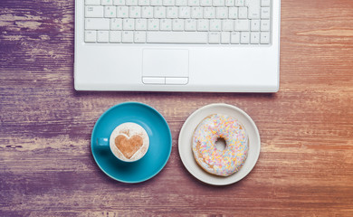 Cup of coffee and donut with notebook on a table.