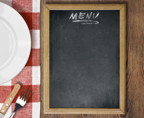Menu blackboard top view on table with dish, knife and fork