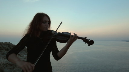 Beautiful violinist playing while the sun is almost gone over